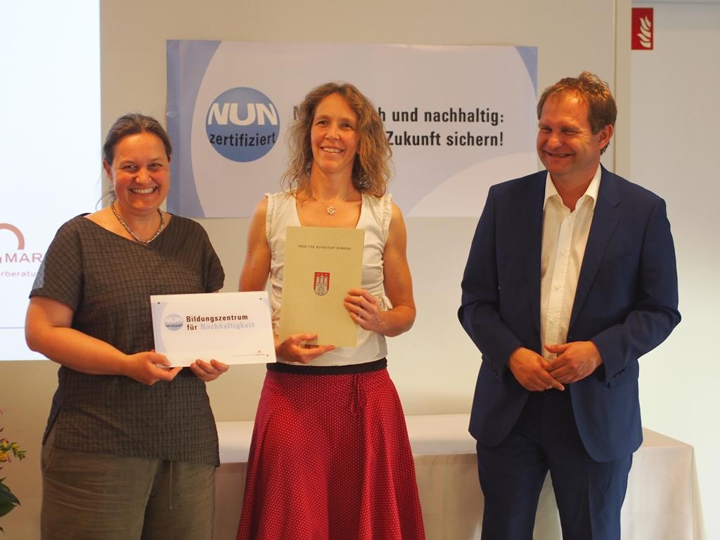Umweltsenator Jens Kerstan übergibt T. Neubüser und C. Zurek das NUN Zertifikat stellvertretend für das Team des Ökomarkt e.V.